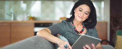 woman sits comfortably reading on tablet computer